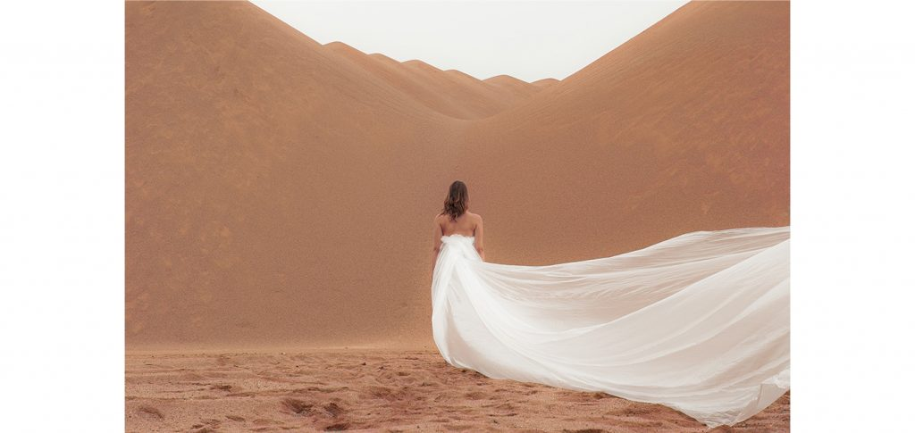 "woman in dessert with long white ""dress"""