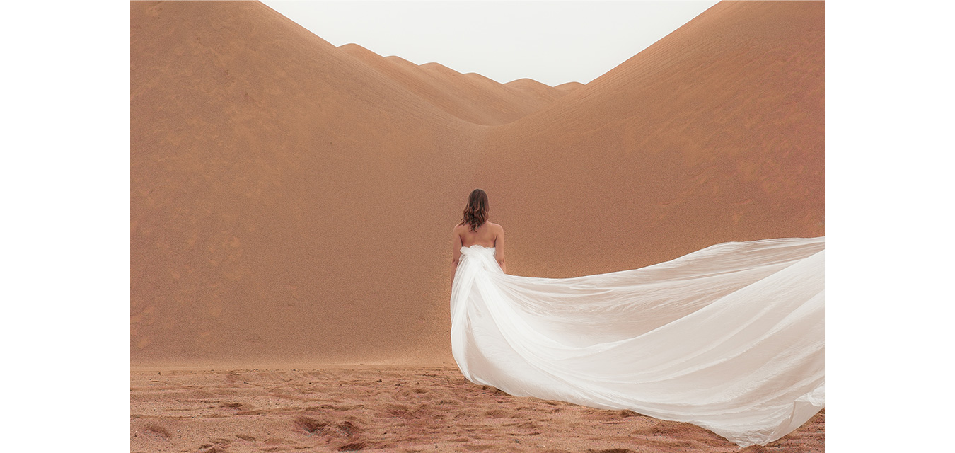 woman in dessert with long white dress